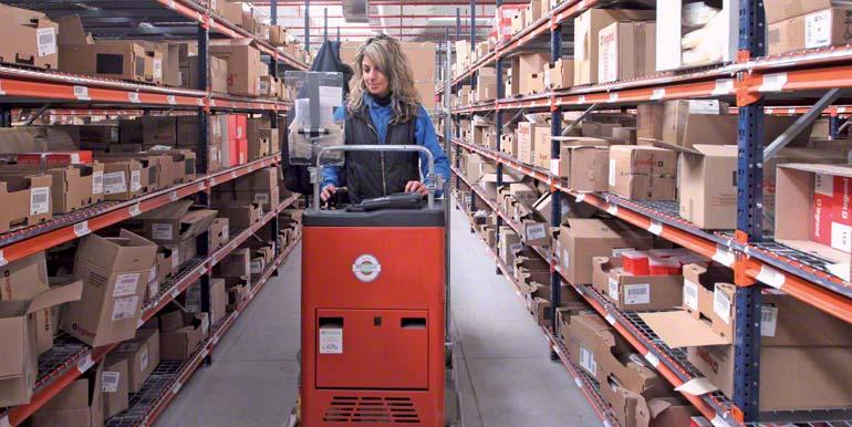 Operátor v průběhu kompletace na nízké úrovni, kterou vykonává pomocí vozíku určeného na provádění kompletace.