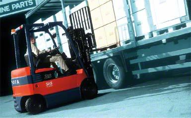 Vozík obsluhující zboží u boku vozidla.